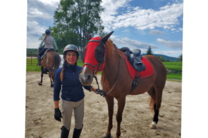 A woman next to a horse wearing a red hood