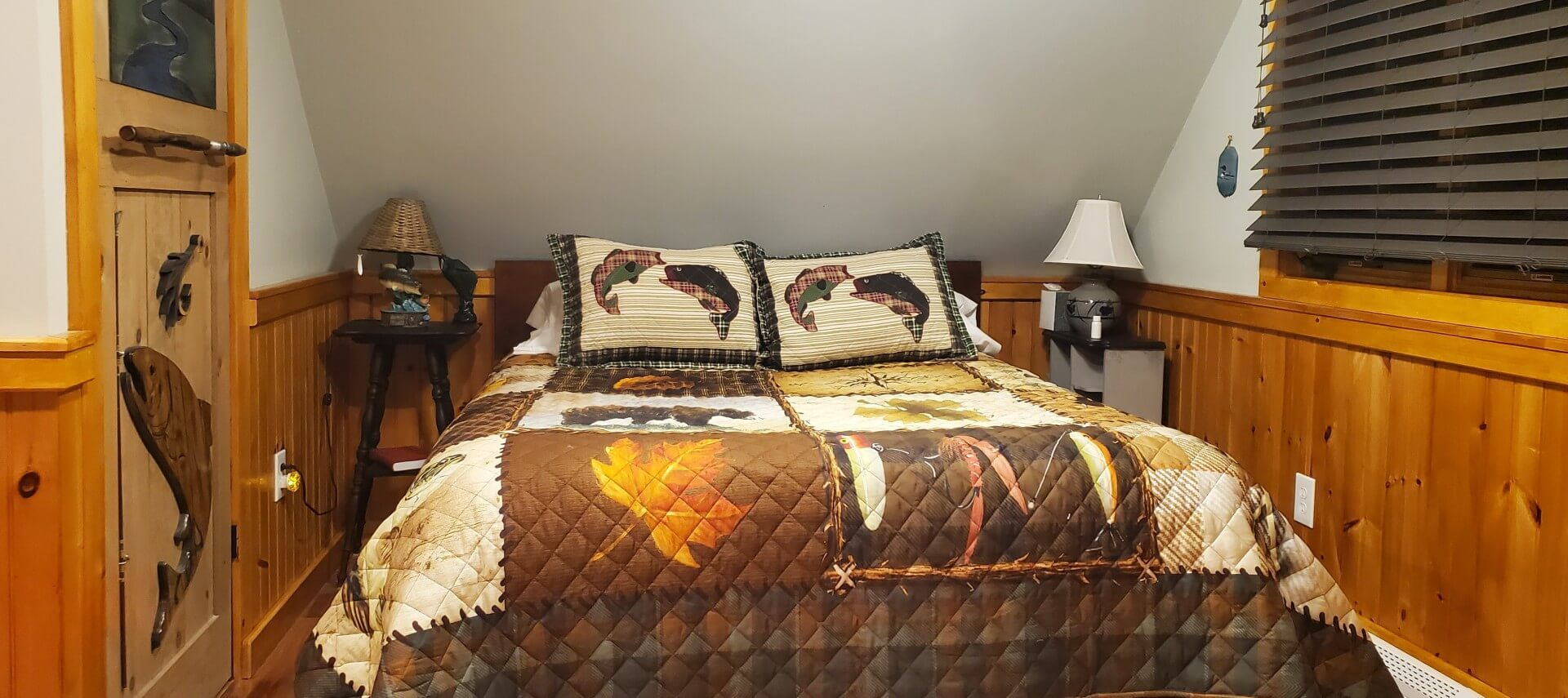 Queen bed with quilt adorned with bears, fish, and maple leaves. A wooden door carved with a fish and river scene is next to the bed.