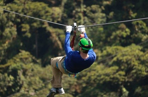 Man in beige pants and a blue shirt ziplining above a forested area