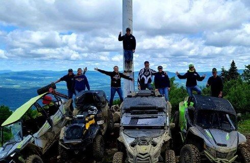 A group of people standing with four ATV machines at the top of a mountain