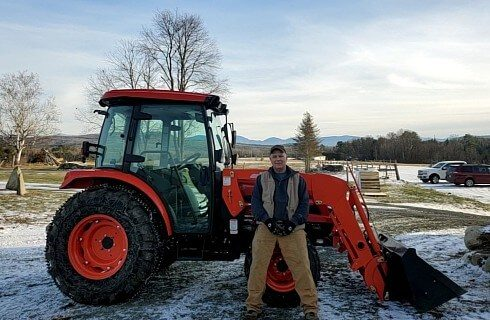Large orange backhoe tractor with a man standing in front