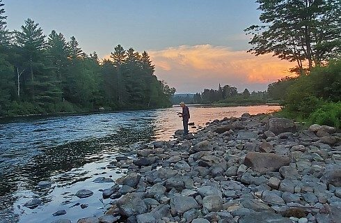 A lone fisherman at the edge of a river with a rocky shore surrounded by trees