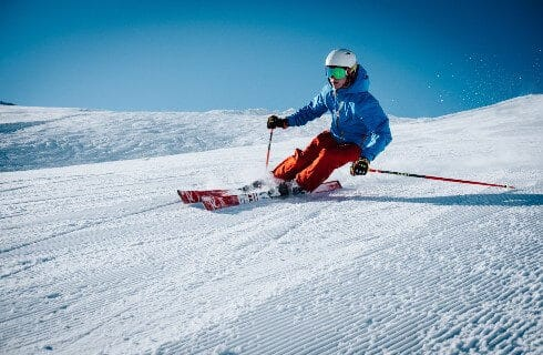 A skier with red pants and a blue jacket coming down a slope with bright blue skies overhead