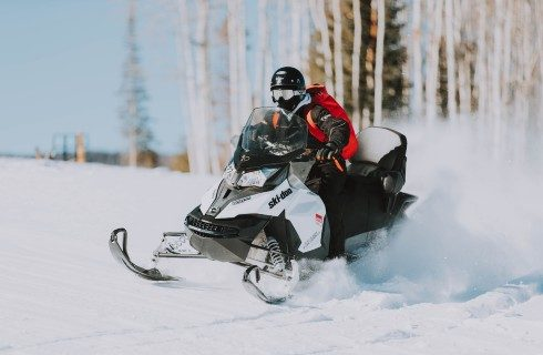 A person in a helmet on a snowmobile driving through the snow with birch trees in the background