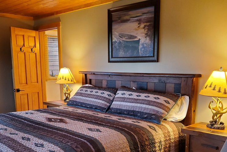 Queen bed with wooden headboard in cozy guest room with antler lamps on bedside tables