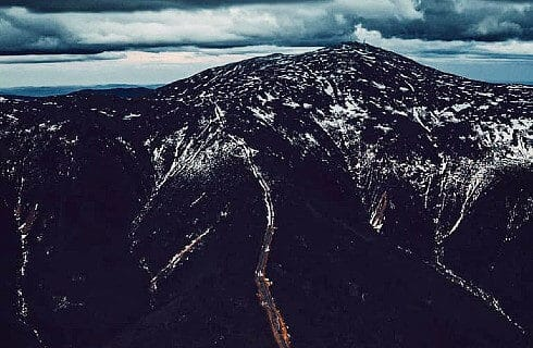 Overhead view of a large mountain range showing road system and snow with dark cloudy skies