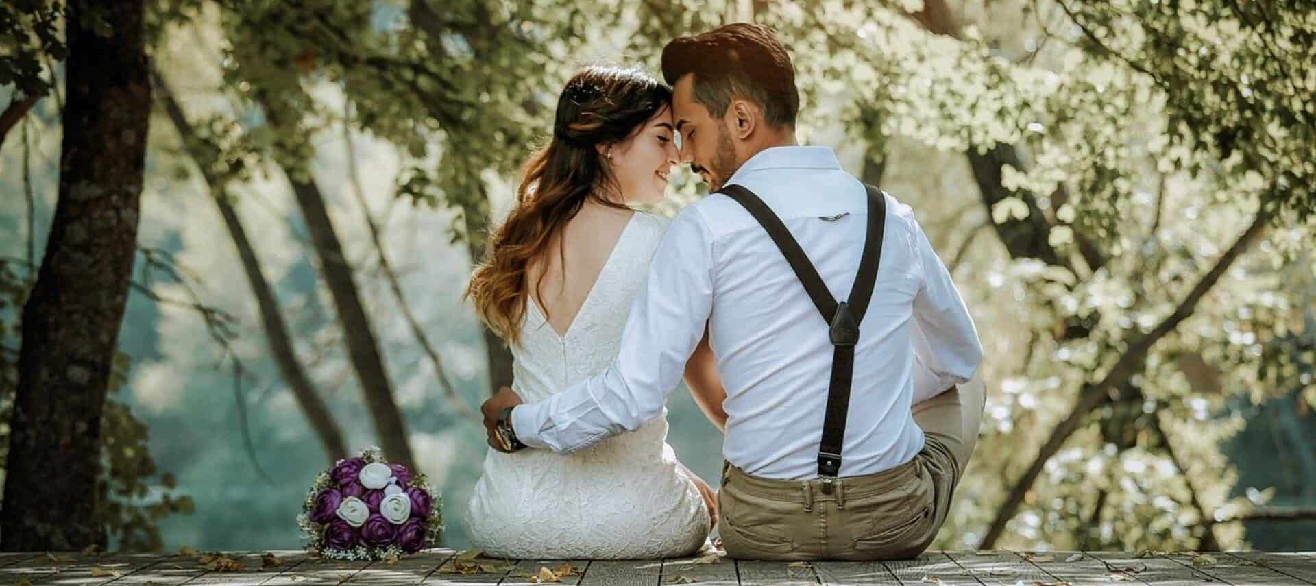 A bride and groom sitting on the edge of a dock facing each other with soft sunlight coming through the trees