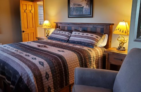 Queen bed with colorful quilt in cozy room with sitting chair and bedside tables with antler lamps