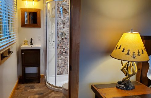 Doorway into a bathroom showing a stand up shower with curved door and single sink vanity