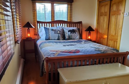 Queen sleight bed in guest room with bright windows, two bedside tables with lamps and a wooden chest