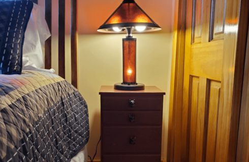 Single bedside table with fox head knobs and amber colored lamp