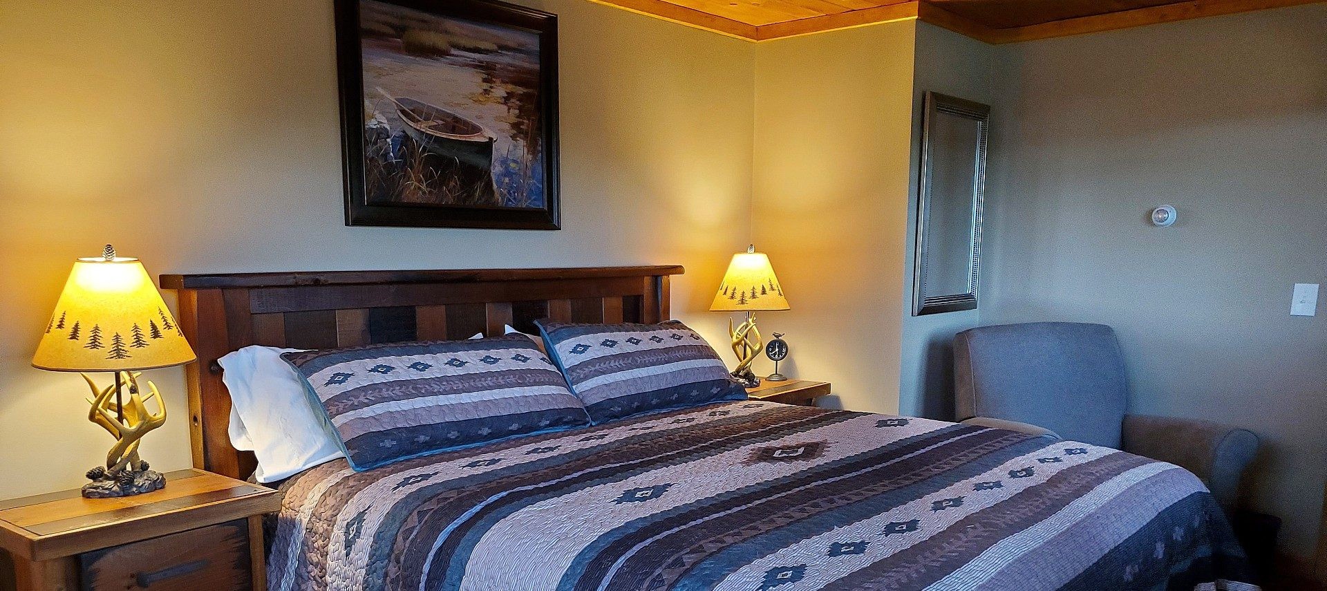 Room with a queen bed, beside tables with antler lamps and a grey sitting chair