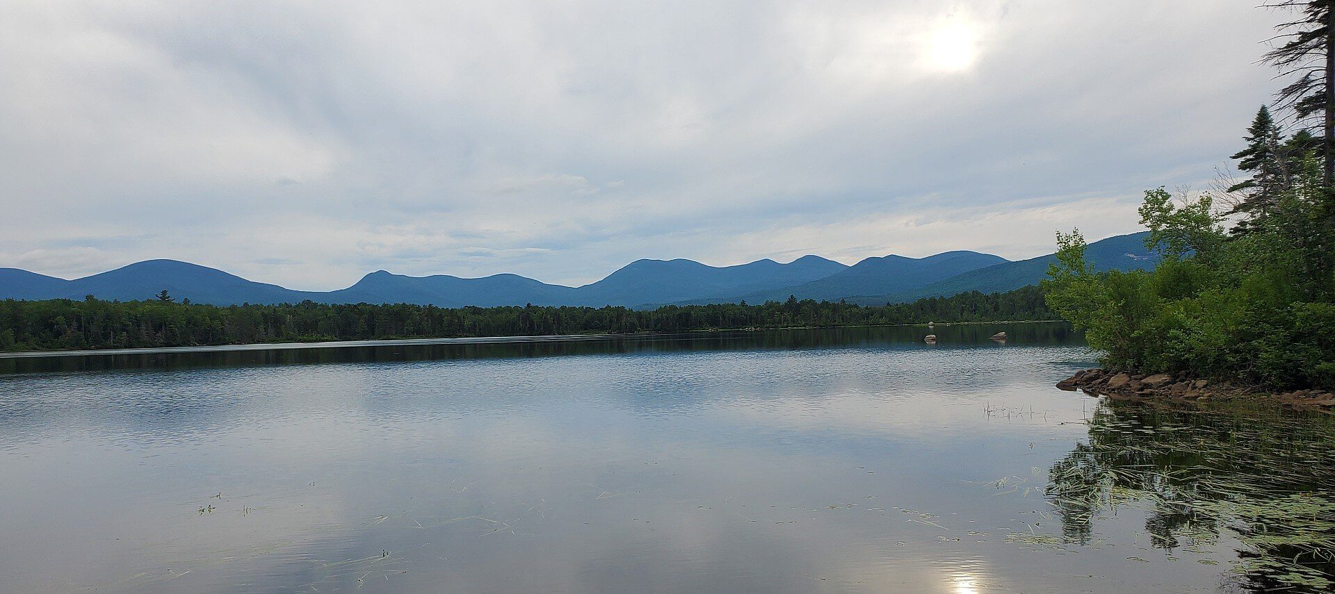 Large calm lake surrounded by trees with a mountain range in the background