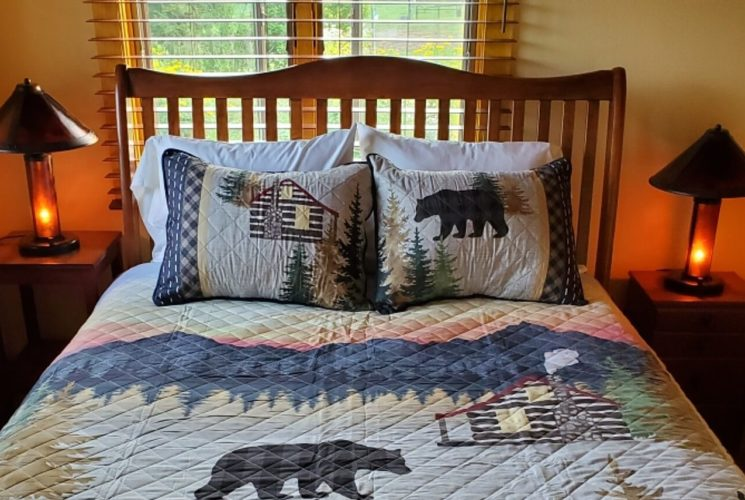 Queen bed with wooden frame, quilt with bears and mountain range and two bedside tables with lamps
