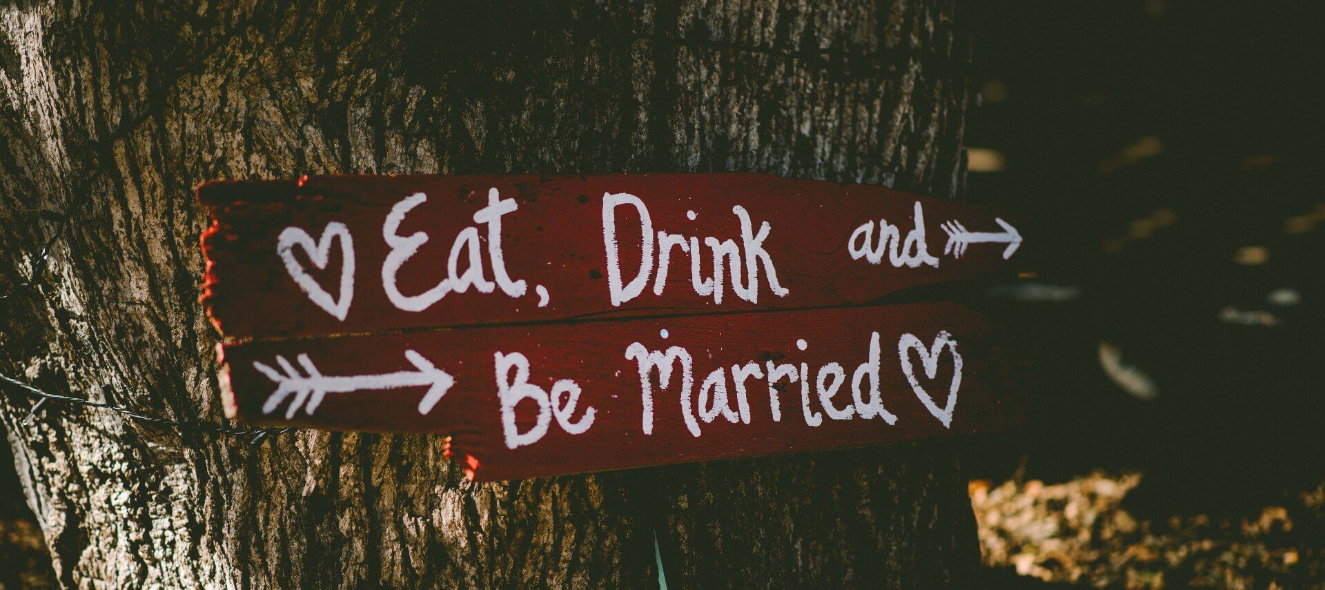 """Red sign with text """"eat, drink and be married"""" nailed to a brown tree trunk"""