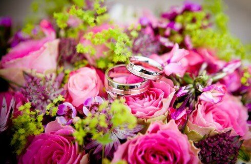 Bouquet of bright pink flowers with two silver wedding bands sitting on top